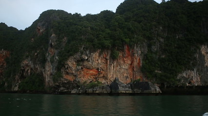 cliff covered with green trees hanging over the dark blue sea