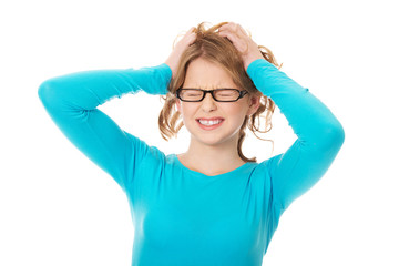 Frustrated teenage woman pulling her hair