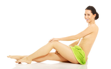 Side view of a woman sitting wrapped in towel on hips