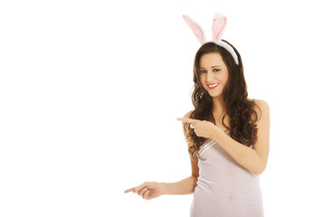 Woman wearing bunny ears and showing copyspace