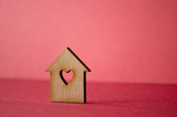 Wooden house with a hole in the form of heart close-up on a red