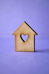 Wooden house with a hole in the form of heart close-up on a purp