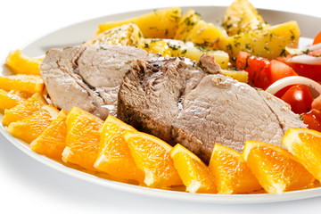 Roasted pork, boiled potatoes and vegetable salad