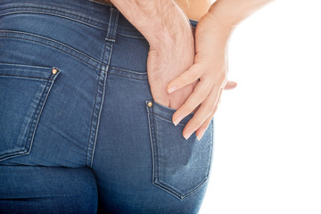 Male hand in woman's jeans pocket.