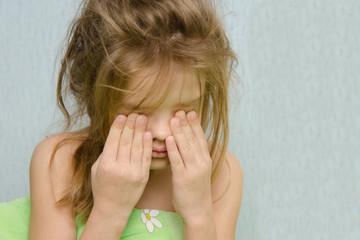 Awakened girl rubbing sleepy eyes