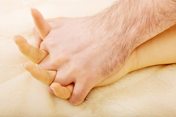 Hands of female and male lying on bed.