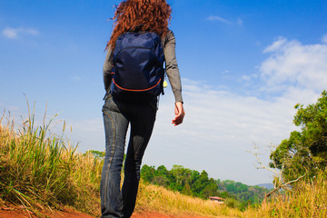 Young woman with backpack is walking on a dusty country road
