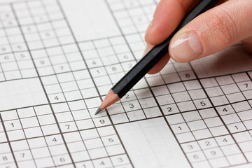 woman hand holding a pencil and solves crossword sudoku.
