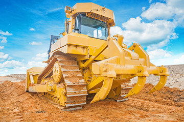 bulldozer yellow colored standing on sand rear view
