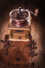 coffee greender with beans on old wooden board