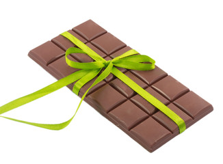 bar of chocolate and green ribbon isolated on white background