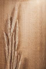 ears of wheat on oak wooden board with copyspace