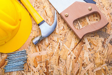 helmet handsaw hammer and nails on old wooden board horizontal v