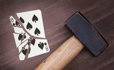Hammer with a broken card, eight of spades