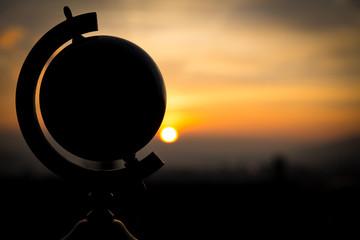 Silhouette eines Globus vor einem Sonnenuntergang, Konzept Reise
