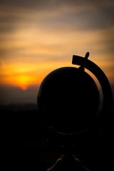 Silhouette eines Globus vor einem Sonnenuntergang, Konzept Fernw