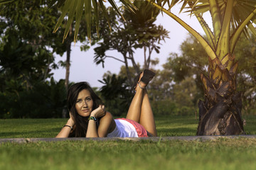 Young woman resting laying on grass in the park