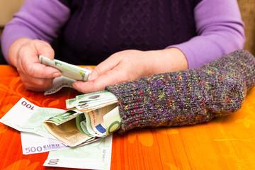 Seniorin zählt Geld im Sparstrumpf