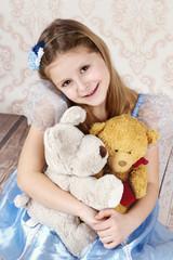 Little girl sitting on the floor holding plush teddy bear