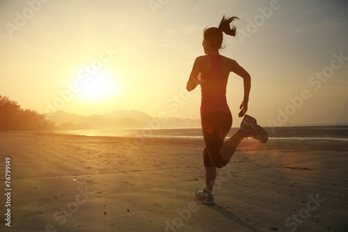 young woman running on sunrise beach - 76799149