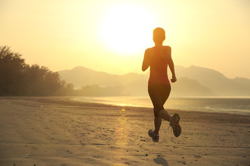 young woman running on sunrise beach