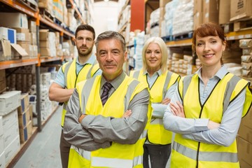 Smiling warehouse team with arms crossed