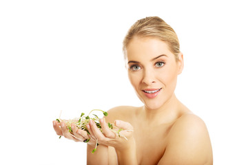 Healthy nude woman holding a cuckooflower