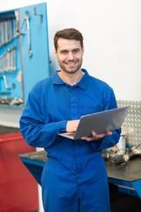 Mechanic smiling at the camera using laptop