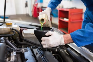 Mechanic pouring oil into car