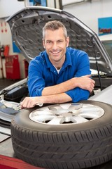 Mechanic smiling at the camera with tire