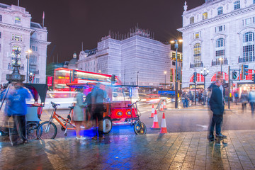 LONDON - SEPTEMBER 27 : Motion blurred traffic and people pass t