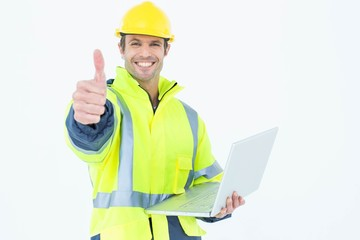 Architect in reflective clothing with laptop gesturing thumbs up