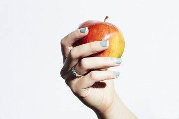 apple in hand with manicure.beauty salon.woman polish