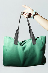 textile handbag in woman hand. fashion green sport bag