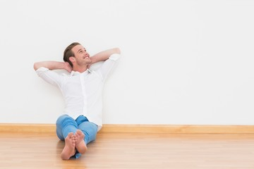 Casual man sitting on floor at home