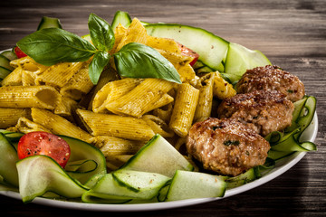 Pasta with pesto sauce, fried chops, parmesan and vegetables