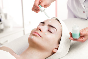 Serum facial treatment of young woman in spa salon