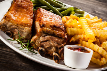 Barbecued ribs, French fries and vegetables