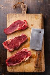 Raw fresh meat Ribeye steak entrecote and meat cleaver on cuttin