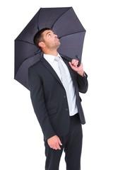 Businessman sheltering under black umbrella