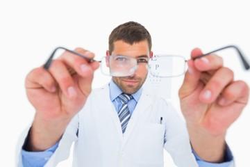 Smiling optician presenting eyeglasses