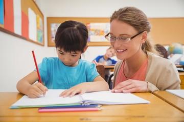 Pretty teacher helping pupil in classroom