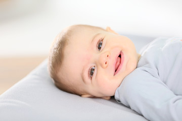 Portrait of smiling baby boy laying on changing table