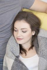 Junge Frau liegt auf Sofa, lehnt sich an ihren Freund