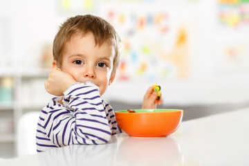 Little boy having breakfast and looking at the camera