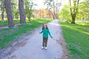 The little girl  playing outdoors in summer. Happy childhood