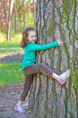 The little girl embraces a big tree playing outdoors in summer.