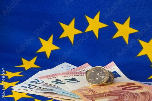 Euro-Münzen und Euro-Banknoten vor der europäischen Flagge