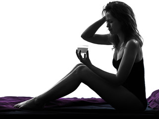 woman taking effervescent medicine in bed silhouette