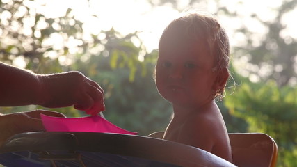 small blonde baby girl feeding on the high chair at sunrise